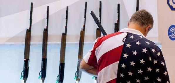 man-in-flag-shirt-examines-guns-nra-596x283.jpg