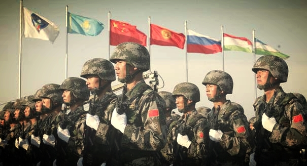 Chinese soldiers march in front of state flags of states member of the SCO during a parade marking the end of military exercises at Chebarkul testing range 17 August 2007. The presidents of Russia, China and four other Central Asian states attended unprecedented joint military exercises on Friday, intended as a display of strength to the West. AFP PHOTO / MAXIM MARMUR (Photo credit should read MAXIM MARMUR/AFP/Getty Images)