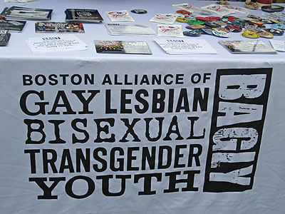 "This outside ""club"" for youth, run by radical adult activists, also had a booth at ""Youth Pride Day."" Note the packages of condoms (round and square) being given out on the table — an indication of what  the  ""club""  is really all about."