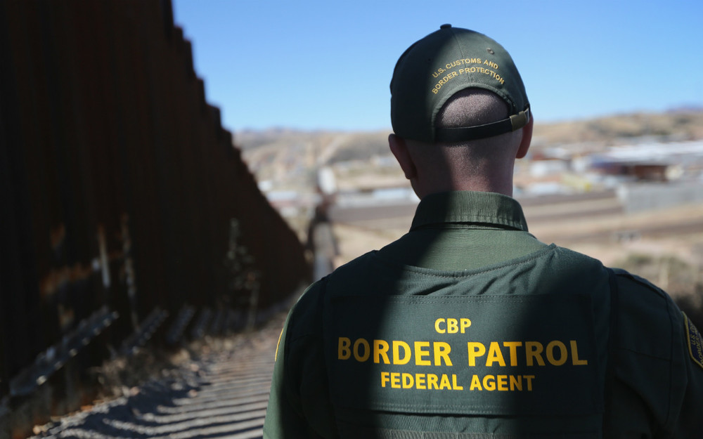 NOGALES, AZ - FEBRUARY 26: A U.S. Border Patrol agent looks along a section of the recently-constructed fence at the U.S.-Mexico border on February 26, 2013 in Nogales, Arizona. The new fencing, which ranges from 18-32 feet high in the Nogales area, allows Border Patrol agents to see through the fence and is harder for immigrants or drug smugglers to scale from the Mexican side. (Photo by John Moore/Getty Images)