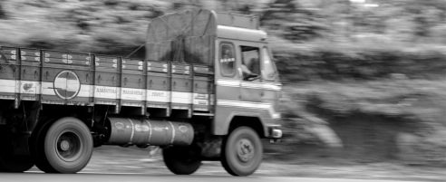 Truck after mining truck race upon the narrow  road through Sakleshpur in Malnad. The dusty load lies flat up to the top edge of the carrier and is never covered.