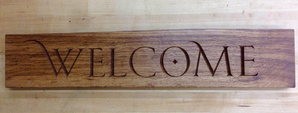 """Welcome plaque, English Brown Oak, 25"""" x 5"""". I am extra excited to announce that this little sign (and more, soon, hopefully) will be available for purchase through the Grovewood Gallery in Asheville, NC. Any folks local to Asheville (you know who you are) should come on down and check it out. #lettercarving"""