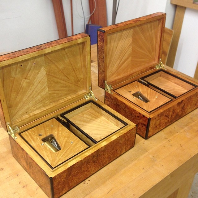 "Music box interiors. The satinwood box is on the left, the narra on the right. Each one has a separate box for the movement itself, as well as a shallow tray with storage space beneath. All the veneer is shop sawn and matched with opposing 6-way ""fans."""