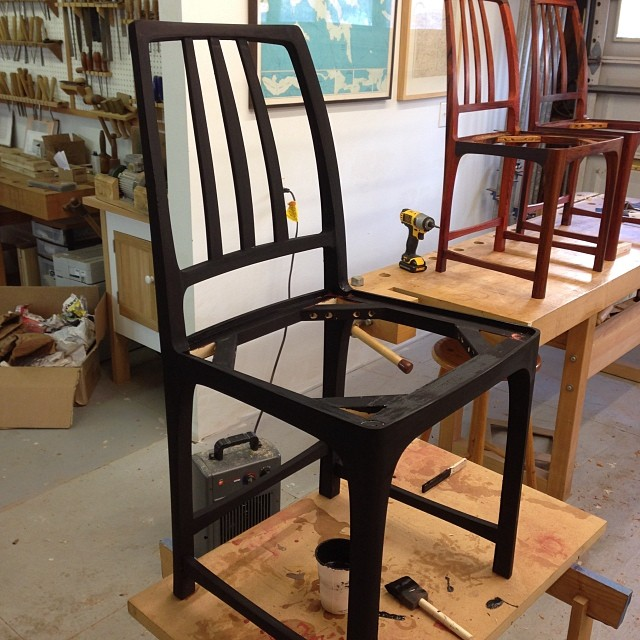 "Second coat of milk paint on the poplar chair. Changed it up from ""Salem Red"" to ""Pitch Black."" Hopefully just one more coat after this, then oil. #blackerthanblack"