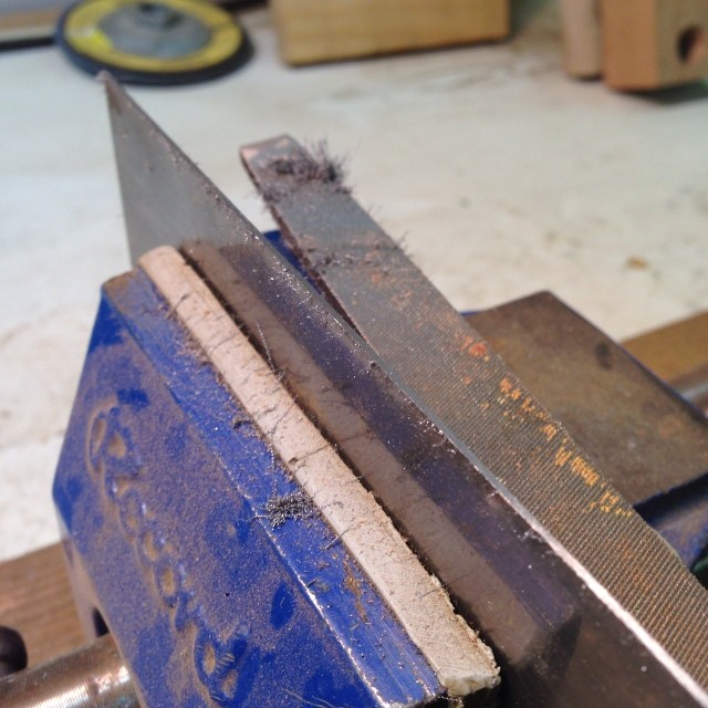 Re-jointing a scraper with a file.