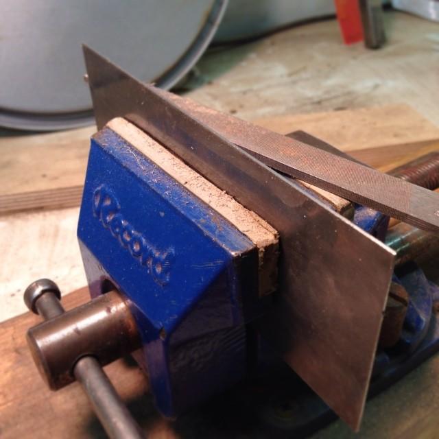 Filing a fresh edge onto a scraper.