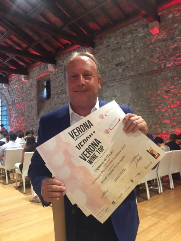 Giambattista Ugolini, owner of Tenute Ugolini, proudly shows his prizes.