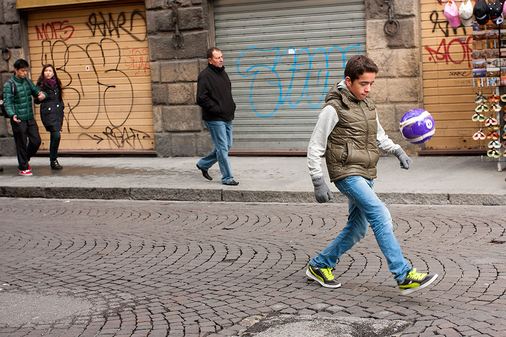 A boy practices his soccer (Futbol) skills, Florence.