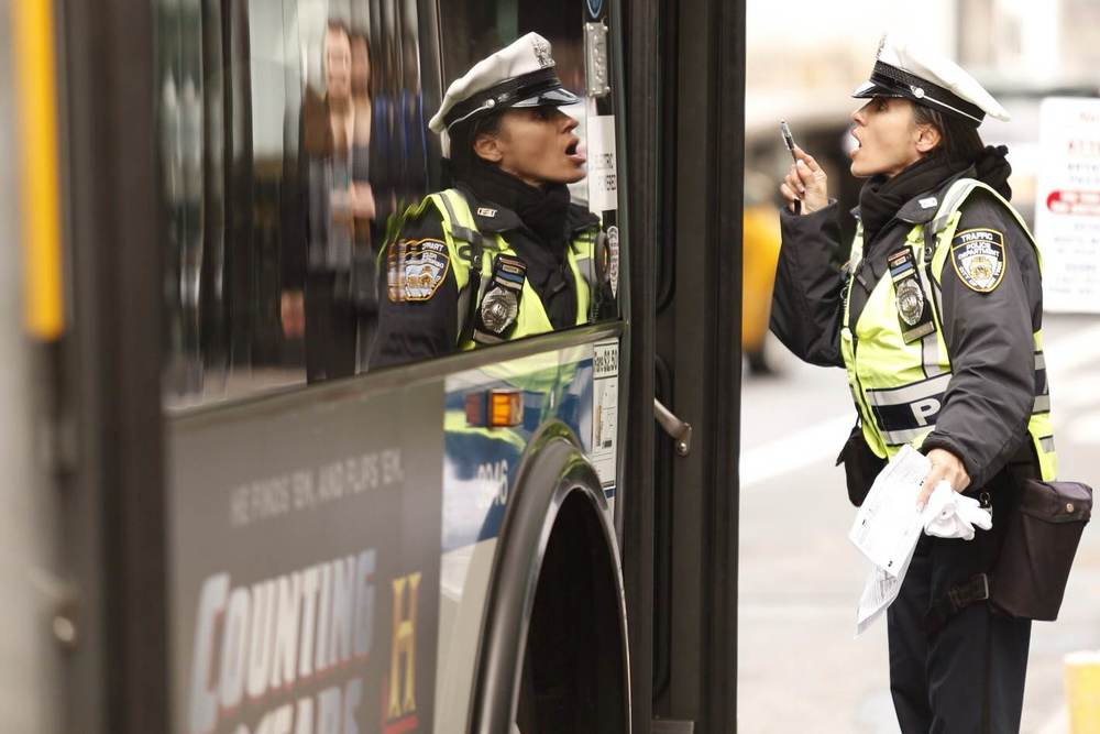 An angry traffic cop hollers at a bus driver near Times Square.