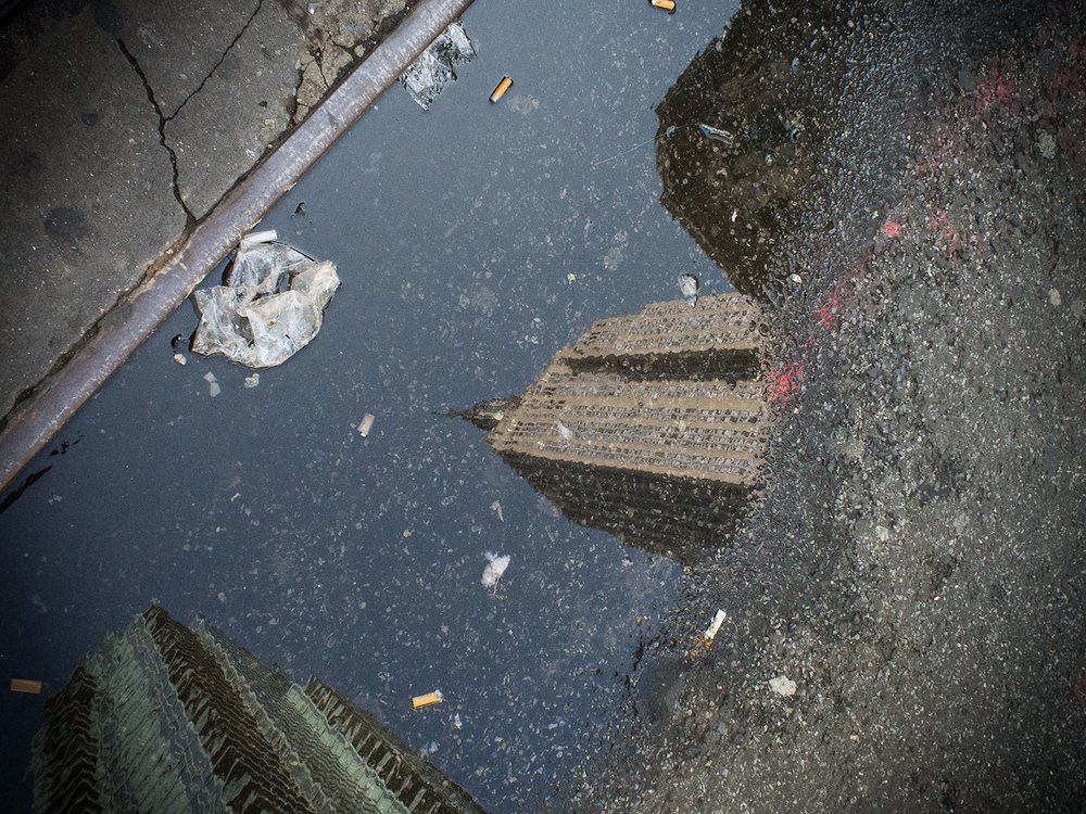 The Empire State Building in a puddle of dirty water.