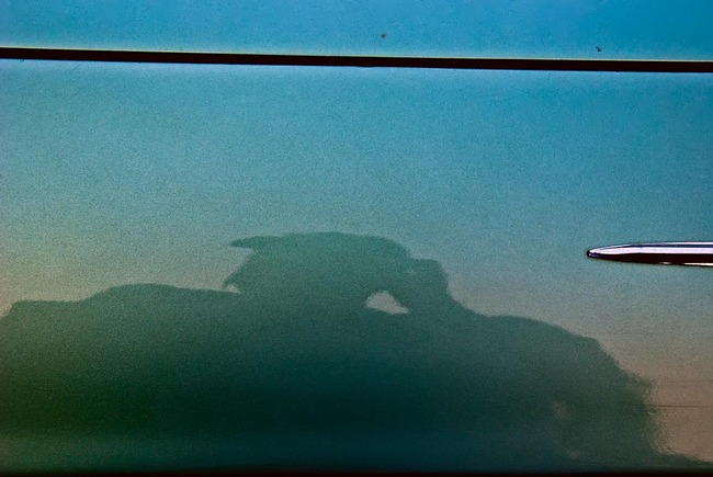 The murky reflection of the photographer in the door of an old, blue car
