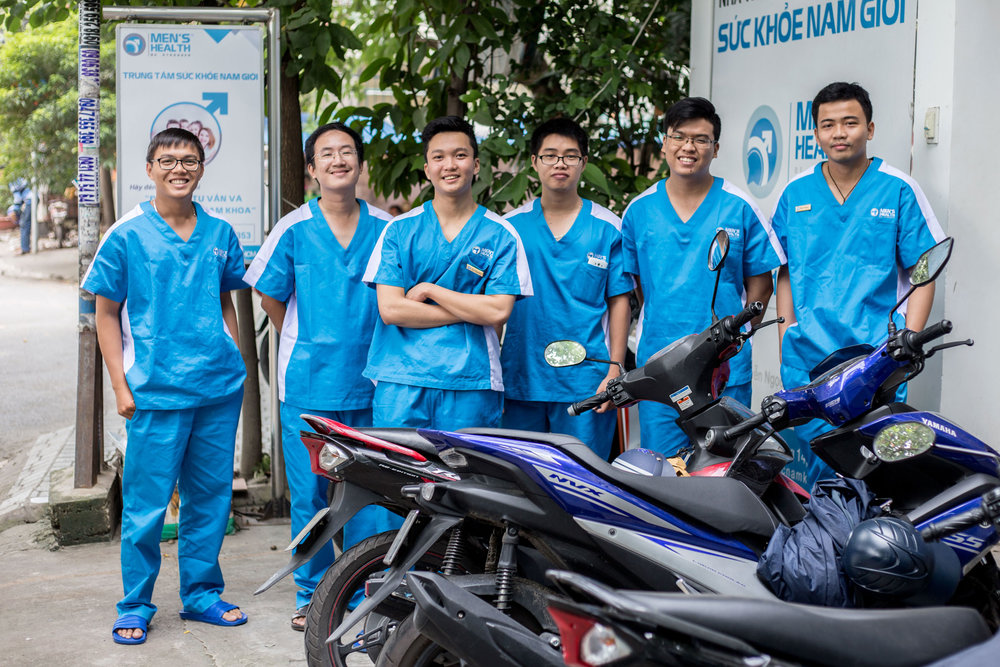 Client  SBS   Project   HIV, aid cuts, and stigma in Vietnam: Healthcare for LGBTQ remains an uphill battle    Caption  The Men's Health Vietnam team pictured outside their clinic in Ho Chi Minh City.