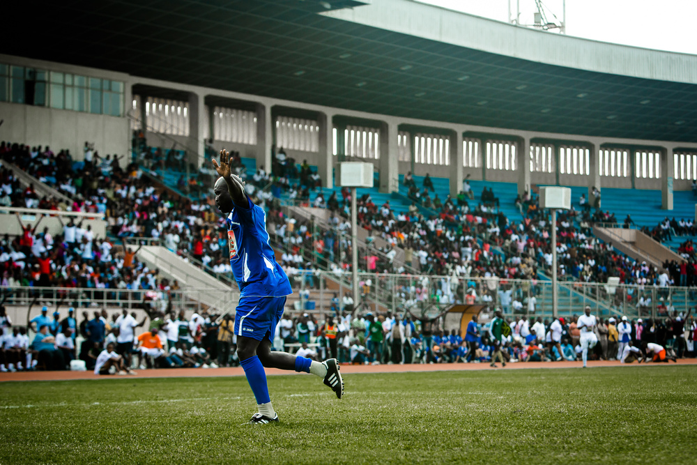 Monrovia, Liberia -  June 22, 2013: George Weah celebrates as the crowd of local Liberians roars after scoring a goal in his Peace Football Match at the Samuel K. Doe Sports Complex in Paynesville.