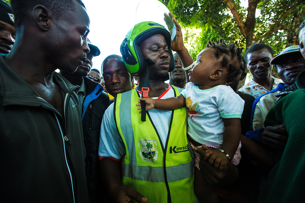 Monrovia, Liberia - November 13, 2013: A pehn-pehn driver at an impromtu rally on Wednesday holding his daughter. The ban is making it difficult to take care of her and the rest of his family. Photo by Morgana Wingard
