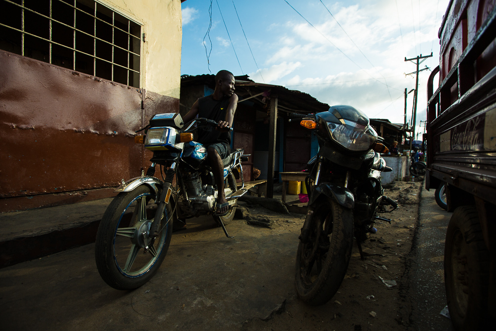 Monrovia, Liberia - November 14, 2013: Musa Sayee Konneh just paid off his bike before the ban. Now he parks it in West Point while he waits until he can use it again. Photo by Morgana Wingard