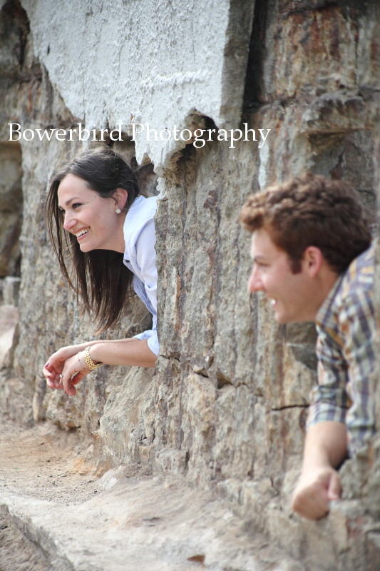 "The couple peeks out of the ""windows"" at the Sutro Baths.  © Bowerbird Photography 2012; Engagement Photography at Lands End, San Francisco."