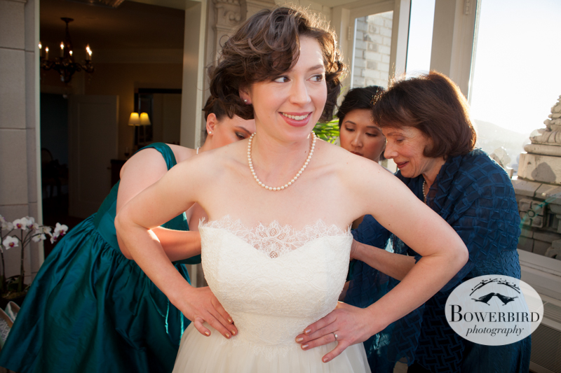 The bride smiles excitedly as she puts on her wedding dress. © Bowerbird Photography 2013; Mark Hopkins Hotel, San Francisco.