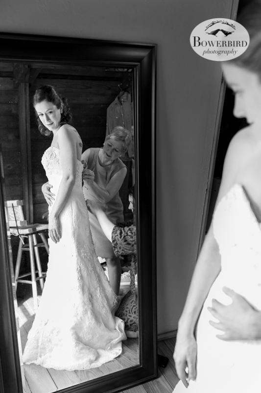 Erica looks at her reflection in the mirror as her mom and dear friend help her put on her wedding dress. © Bowerbird Photography 2013; Lesbian wedding in Bastrop, Texas at Cedar Bend.