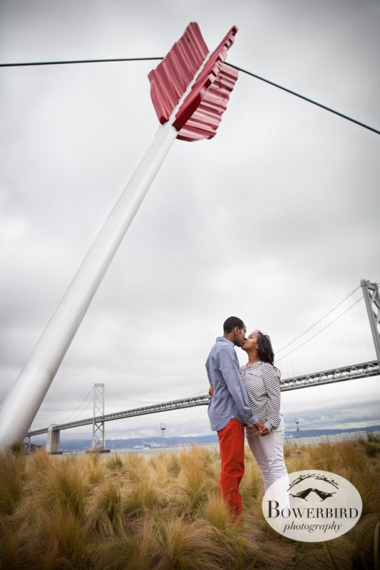 A kiss under the bow and arrow with the Bay Bridge. © Bowerbird Photography 2013; San Francisco Engagement Photo.