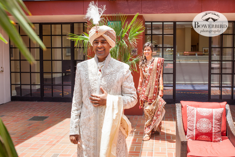 The first look! The groom waits on the balcony to see his bride for the first time before the wedding. Love their expressions of excitement and anticipation! © Bowerbird Photography 2013, First Look, South Asian Wedding at the San Francisco JW Marriott and Winery SF on Treasure Island.