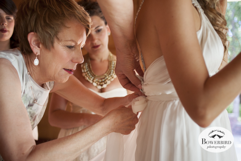 Susie mom helps her put on her wedding dress, and her future mother-in-law also lends a hand. (Kunde Family Estate Wedding Photography in Kenwood. © Bowerbird Photography 2014)