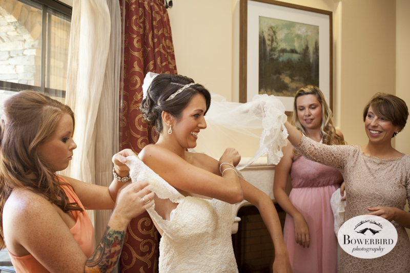 Everyone lends a hand to help the bride put on her wedding dress in her bridal suite at the Meritage Resort & Spa. © Bowerbird Photography 2014