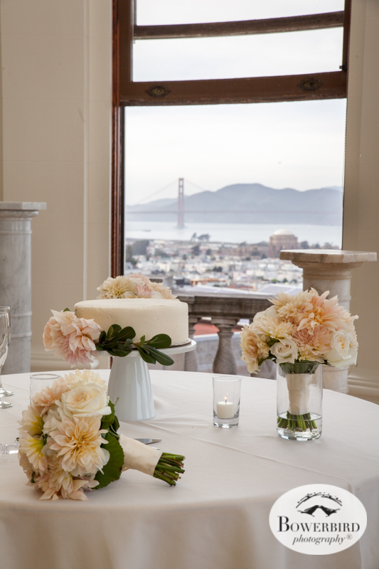 James Leary Flood Mansion Wedding in San Francisco. The wedding cakes and bride's bouquet with a view of the Golden Gate Bridge from the wedding reception hall. © Bowerbird Photography 2016