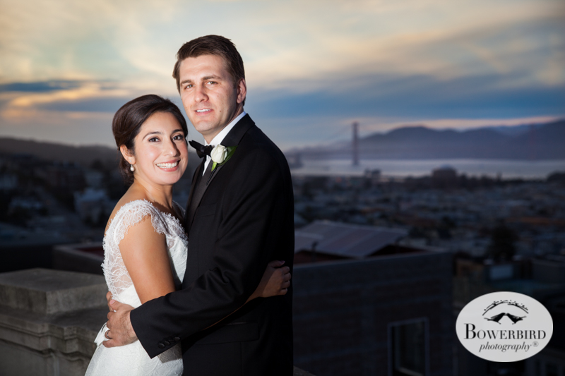 James Leary Flood Mansion Wedding in San Francisco. The bride and groom on the balcony at sunset with a view of the Golden Gate Bridge. © Bowerbird Photography 2016