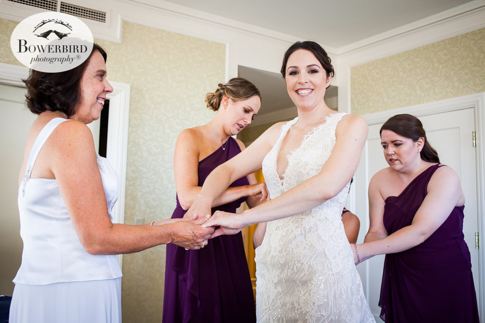 Mom helps the bride put on her stunning wedding dress. Mark Hopkins Hotel wedding prep photos. © Bowerbird Photography 2016