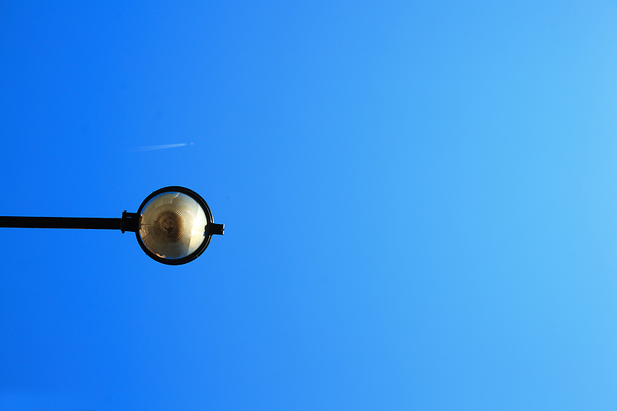 Streetlamp with something flying in the air behind it.