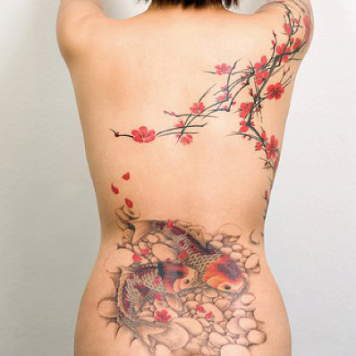 Tattoo of koi in a pond beneith a flowering tree