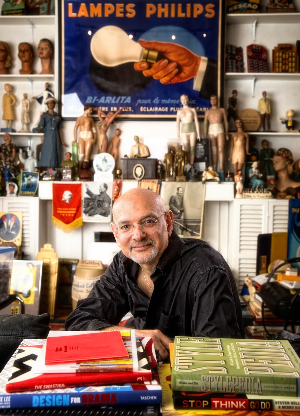 On a recent Saturday morning Steve Heller met me on the steps of his 16th Street studio in Manhattan. I was intent on photographing this icon of design amidst what proved to be the most intense personal collection of objects and books that I had ever seen.       Steve is the latest subject in my graphic designer portrait series. He was the noted art director of the New York Times Book Review for 33 years. He has authored and co-authored over 100 books on design and popular culture. He is a fascinating subject whose charm and accomplishments would be difficult to convey in a single photograph.      My biggest challenge was finding a place to put my camera and tripod. I wedged myself into a tiny space between teetering towers of rare books and objects, terrified that I could knock something over and start an avalanche. (Click on photo to enlarge)