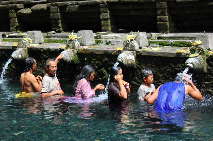 Balinese family moving through the line of water spouts