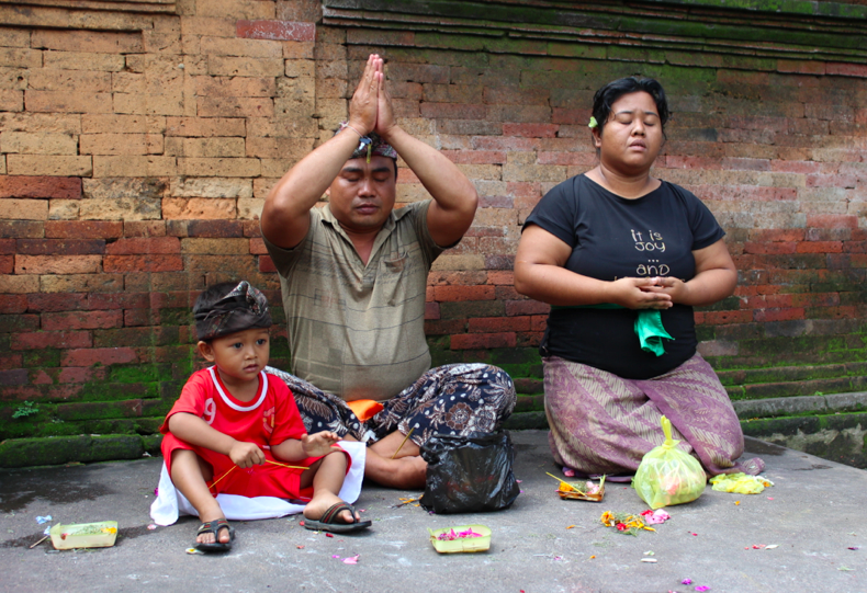 A sarong-clad family praying and leaving offerings