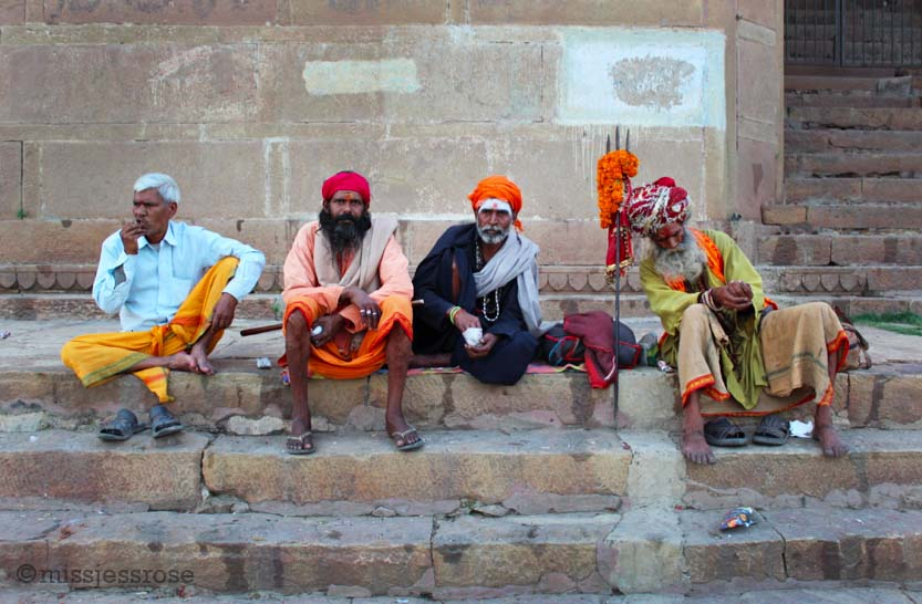 Holy men sitting by the Ganges river in Varanasi