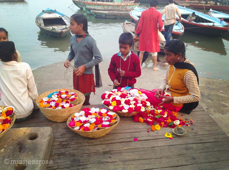 Preparing small floral offerings next to the Ganges