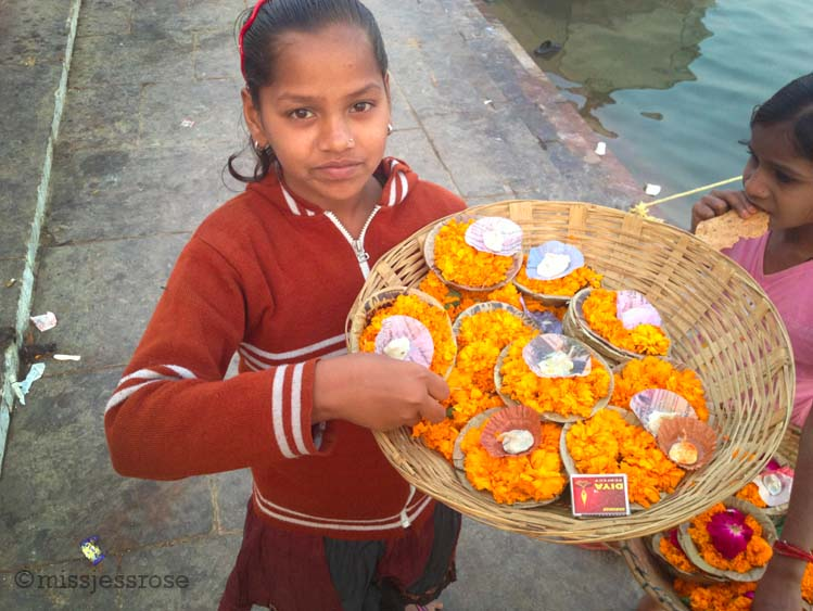 Children selling floral offerings next to the Ganges