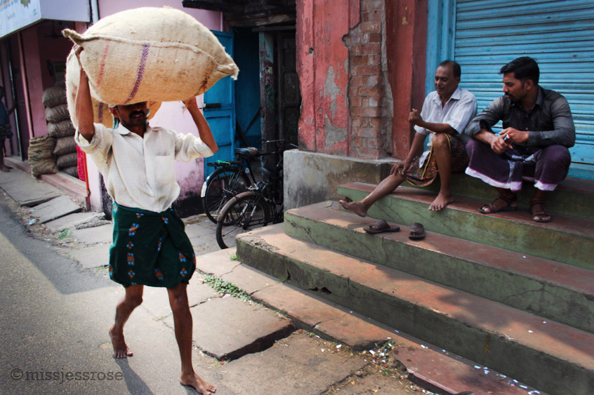 Workers haul large sacks filled with spices and other foods