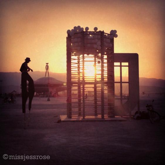 Stilt-walker, the man, and a giant beer sculpture