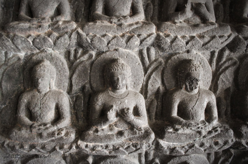 Hundreds of small Buddha carvings cover the two entry walls of one of the caves