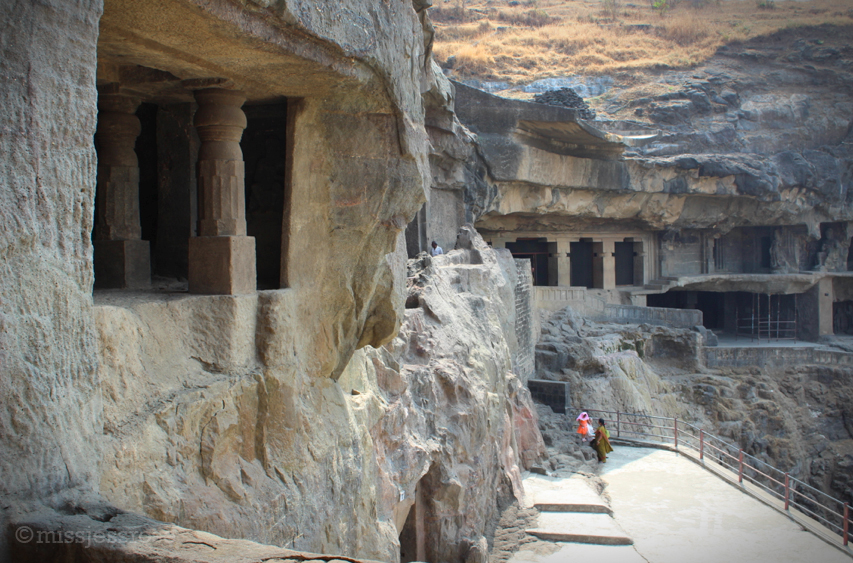 The exterior of Ellora caves, which are carved into a basalt rock cliffside.