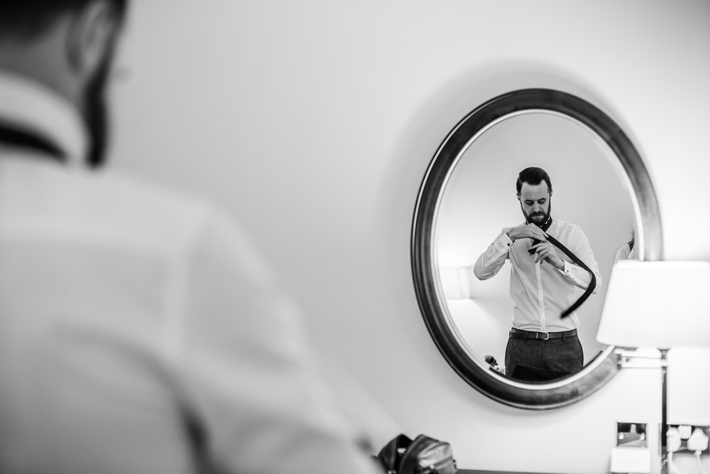 reflection of a groom getting ready