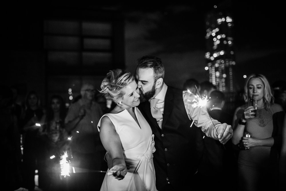 a bride and groom laugh with sparklers on the roof of great john street hotel manchester