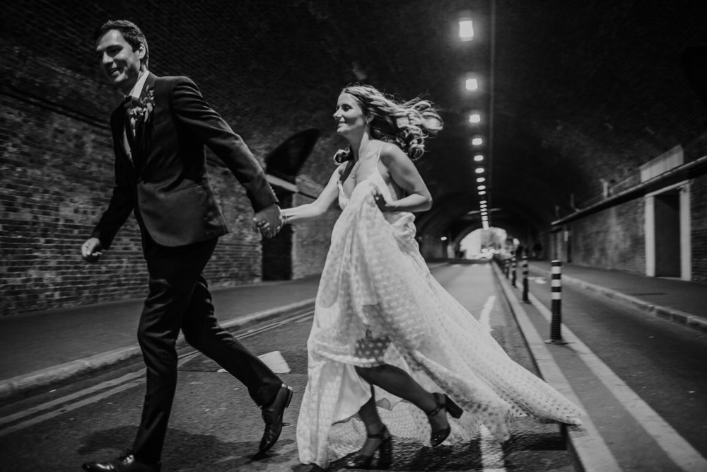 A bride and groom run through a tunnel outside the Taner Warehouse London