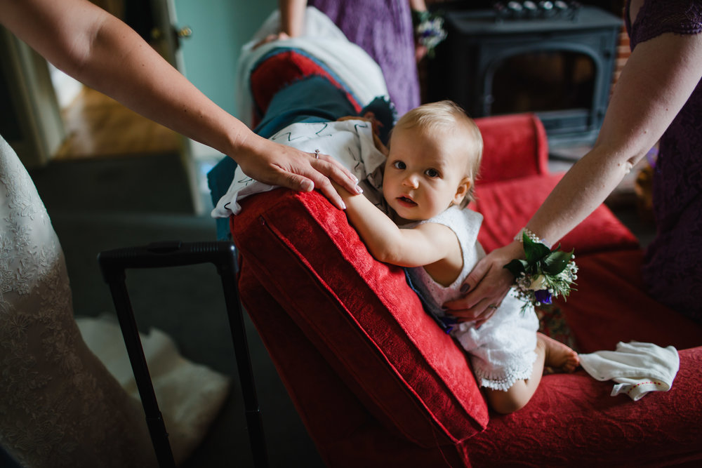 A bride holds the hand of her baby daughter as she dresses for her wedding in Norfolk