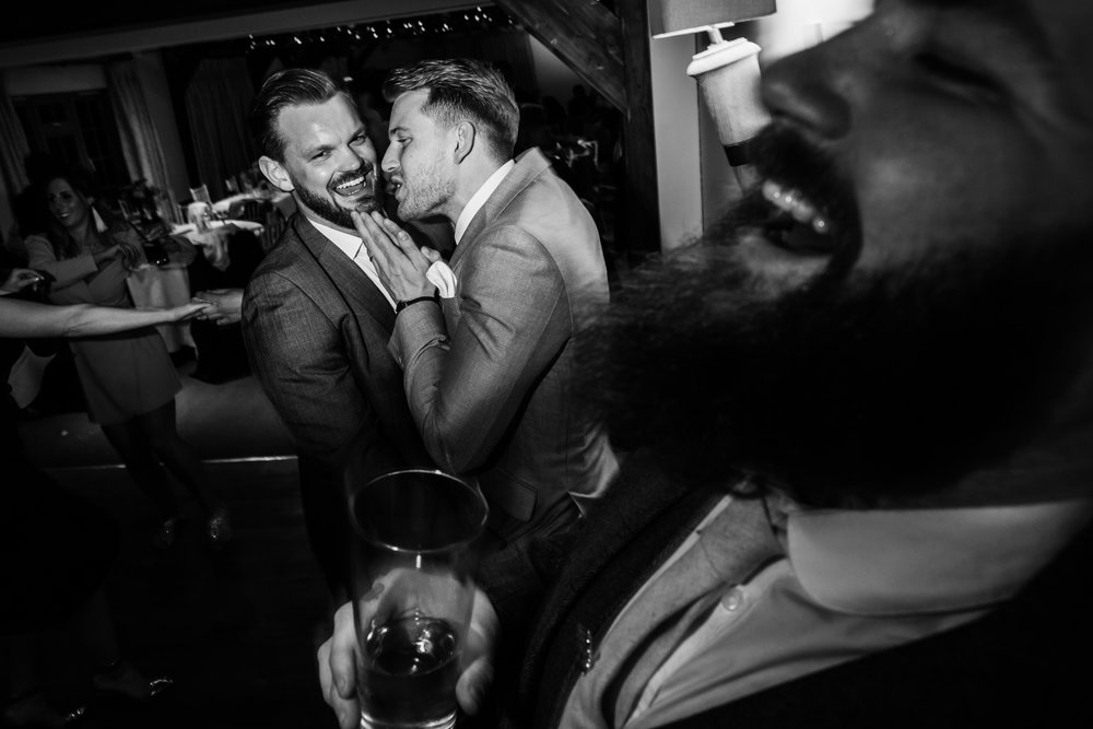 a groom laughs while his friends joke around at the compasses at pattiswick