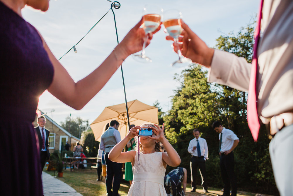 wedding guests toast with champagne while a child takes a picture