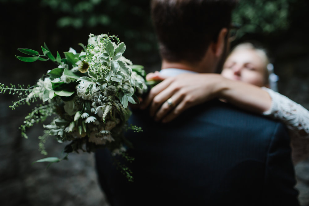 a bride and groom cuddle after a wedding.the bride is holding flowers