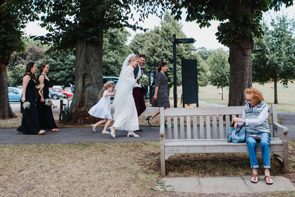 a wedding party walks through a park in twickenham while an old lady watches on.