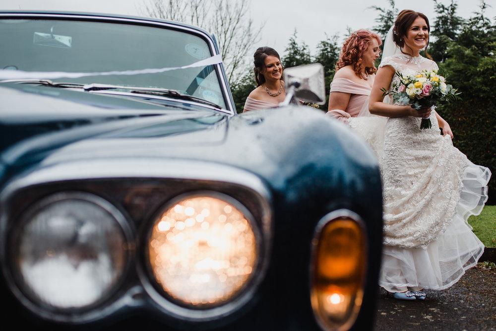 a bride and her bridesmaids arrive at a wedding in a rolls royce